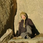 A woman in a knitted hat sitting against a large boulder
